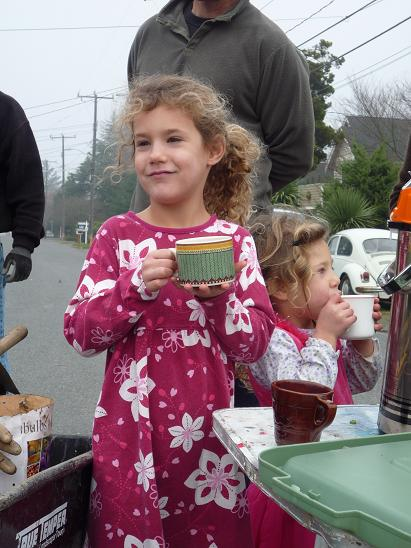 Annika is drinking hot cider after helping plant crocuses in the traffic circle